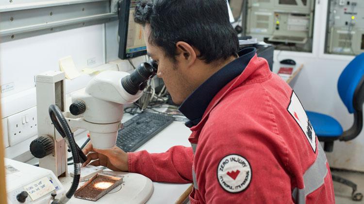 A researcher in a lab using a microscope.